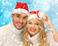 Family couple in sweaters and santa's hats Royalty Free Stock Image
