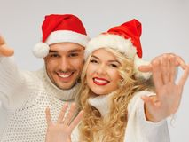 Family couple in sweaters and santa's hats Stock Photos