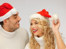 family couple in sweaters and santa's hats Royalty Free Stock Images