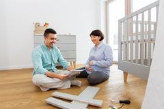 Family couple with user manual assembling baby bed. Parenthood, family and nursery concept - happy middle-aged men and his pregnant wife with user manual stock photography