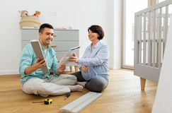 Family couple with user manual assembling baby bed. Pregnancy, family and nursery concept - happy middle-aged men and his pregnant wife with user manual royalty free stock photo