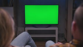 Family Couple Watching Green Screen TV Sitting on Couch in Living Room Together