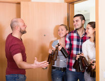 Family couple welcoming visitors at home. Family couple welcoming smiling russian visitors with beer bottles at home royalty free stock photo