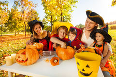 Family crafting Jack-O'-Lantern from pumpkin Stock Images