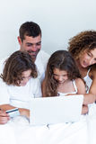 Family with credit card shopping online on bed Royalty Free Stock Image