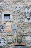 Family Crests on Stone Wall. Several family crests are embedded on the stone wall of an old building in Cortona, Italy, essentially displaying the varied and stock images