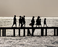 Family crossing bridge. Silhouette of family walking across a bridge over the ocean Royalty Free Stock Images