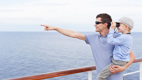 Family cruising. Handsome young father holding his little son looking through binoculars, both enjoying cruise ship vacation together Stock Images