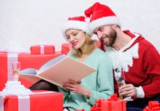 Family cuddle drink champagne near christmas tree while looking family photo album. Remember bright moments of year. Celebrating new year together. Couple in royalty free stock image