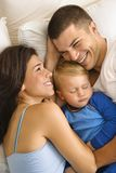 Family cuddling. Caucasian mid adult parents cuddling with toddler son sleeping in bed royalty free stock photos