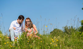 Family cuddling sitting on meadow Stock Image