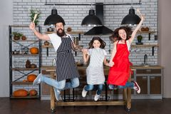 Family cuisine. Home interior. Culinary school. Happy family in kitchen. Mother and father with little girl. Little girl stock photography