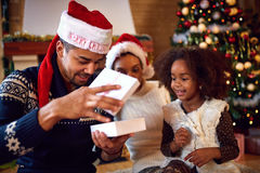 Family curious look at open box with Christmas gift Stock Photos