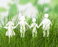 Family cut out paper figures in grass on abstract green. Royalty Free Stock Photos