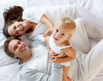 Family with cute little girl playing in bed Stock Photography