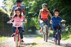 Family On Cycle Ride In Countryside. Smiling At Camera Whilst Wearing Helmets Stock Photography
