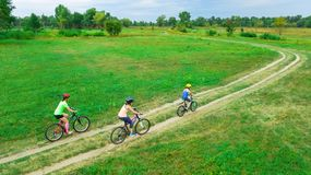 Family cycling on bikes outdoors aerial view from above, happy active mother with children have fun. Family sport and fitness Royalty Free Stock Images