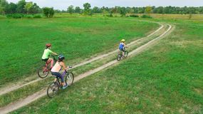 Family cycling on bikes outdoors aerial view from above, happy active mother with children have fun, family sport. And fitness Royalty Free Stock Photos
