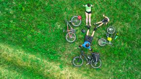 Family cycling on bikes outdoors aerial view from above, happy active parents with child have fun and relax on grass. Family sport and fitness on weekend Stock Photo