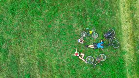 Family cycling on bikes outdoors aerial view from above, happy active parents with child have fun and relax on grass Stock Photography