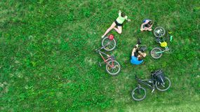 Family cycling on bikes outdoors aerial view from above, active parents with child have fun and relax on grass, family sport stock photography