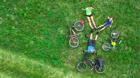 Family cycling on bikes outdoors aerial view from above, active parents with child have fun and relax on grass, family sport. Family cycling on bikes outdoors Royalty Free Stock Photos