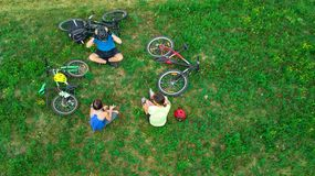 Family cycling on bikes outdoors aerial view from above, happy active parents with child have fun and relax on grass, family sport. And fitness on weekend Stock Image