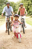 Family Cycling In Countryside Wearing Safety Helme. Ts Smiling At Camera Royalty Free Stock Photos