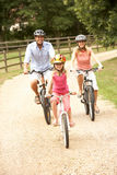 Family Cycling In Countryside Wearing Safety Helme Royalty Free Stock Photos