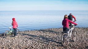 Family cycling. Next to sea Stock Image