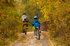 Family cycling outdoors, golden autumn in park Stock Photo