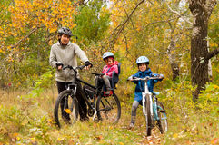 Family cycling outdoors, golden autumn in park Stock Photography