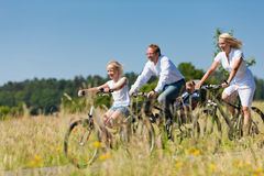 Family cycling outdoors in summer Stock Image