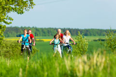 Family cycling outdoors in summer Stock Photos