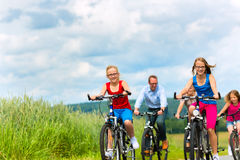 Family cycling in summer in rural landscape Royalty Free Stock Images