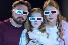 Family in 3d glasses watching movie and holding popcorn Royalty Free Stock Images
