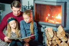 Family reading a book together near fireplace on Christmas eve stock photo