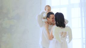 Family, dad, mom, baby in white clothes with angel wings mom stock footage