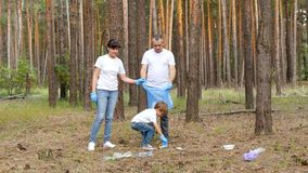 Family: dad, mom and child volunteers collect garbage in the woods. Attitude to the environment, protection of nature