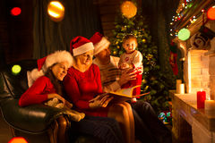Family - dad, mom with daughters sitting on sofa and reading book near by fireplace Stock Photo