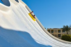 A family of dad and son ride a tubing on a fast water attraction in an aquapark stock photo