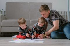 Family dad and two twin brothers draw together markers and felt pens sitting on the floor. Family dad and two twin brothers draw together markers and felt pens royalty free stock photography