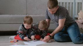 Family dad and two twin brothers draw together markers and felt pens sitting on the floor. Family dad and two twin brothers draw together markers and felt pens stock footage