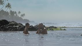 Family of daddy and son has fun in ocean bay slow motion