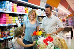 Family in dairy section in supermarket. Positive young family shopping various dairy products in supermarket Stock Photo