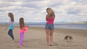 The family dances on the beach. They are not professional dancers. They are fun and they are funny. In video a mother and two daughters. Slow motion stock video