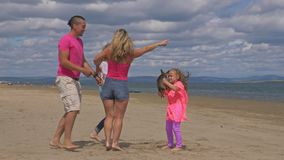The family dances on the beach. They are not professional dancers. They are fun and they are funny. In video a parents with two daughters and two dogs stock video