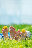 Family with dandelion  flowers lying on green grass in sunny day Royalty Free Stock Image