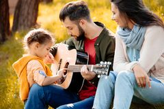 Family with daughter relaxing on a grassy hill while father is playing. The guitar royalty free stock images