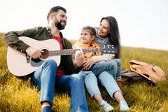 Family with daughter relaxing on a grassy hill while father playing. The guitar royalty free stock images